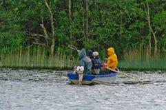 钓鱼在小船的年轻人 库存照片