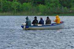 钓鱼在小船的年轻人 免版税库存图片