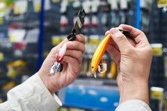 钓鱼在手人的诱剂诱饵在商店 免版税库存照片