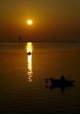 钓鱼在日出的小船 免版税库存图片