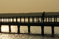 钓鱼在日出的桥梁 图库摄影