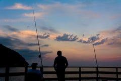 钓鱼在日落期间的两个人 图库摄影