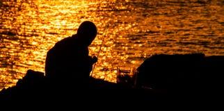 钓鱼在日落的孩子剪影 免版税库存照片