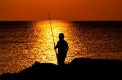 钓鱼在日落的孩子剪影 免版税库存图片