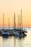 钓鱼在日落的小游艇船坞码头和人 库存图片