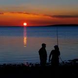 钓鱼在日落的比目鱼的在海滨 免版税库存照片