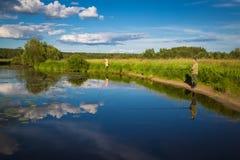 钓鱼在有百合的湖在农村地点 图库摄影
