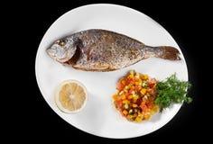 钓鱼在有菜和柠檬的一块板材烤的格栅盘被烘烤的整个在菜单的上面 免版税库存图片