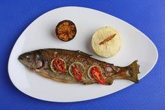 钓鱼在有菜和柠檬的一块板材烤的格栅盘被烘烤的整个在上面 免版税库存照片
