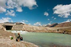钓鱼在有迅速流程的一条山河的老人和年轻男孩在云彩下 免版税库存图片