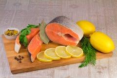 钓鱼在桌和绿色安置的三文鱼、柠檬。 图库摄影