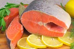 钓鱼在桌和绿色安置的三文鱼、柠檬。 库存图片