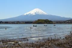 钓鱼在河口湖的渔夫和富士山 免版税库存照片