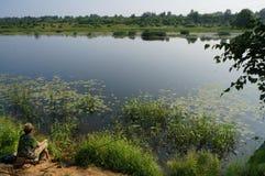 钓鱼在河海岸  免版税库存图片