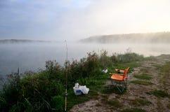 钓鱼在河的供应在雾的早晨 图库摄影
