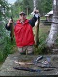 钓鱼在河 一个人在他的手上拿着两支大矛 活跃室外休闲 免版税库存照片
