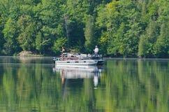 钓鱼在浮船小船的男人和妇女 免版税库存图片