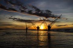 钓鱼在海的渔夫在日出 免版税图库摄影
