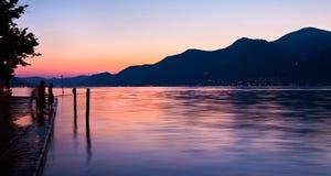 钓鱼在湖岸的日落的孩子 免版税库存照片