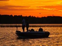 钓鱼在湖的一条小船的人剪影在日落以后 库存照片