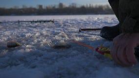 钓鱼在湖的冬天的一位老人渔夫 捕鱼冰谎言捕捉冬天zander 渔夫钓鱼捕鱼漏洞冰冬天 4K 影视素材