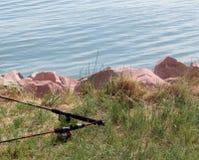 钓鱼在湖的桃红色岩石附近 库存图片