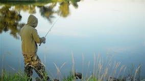 钓鱼在湖的鱼人在春天 停留孤零零的钓鱼者天生单独围拢 他有休息 影视素材