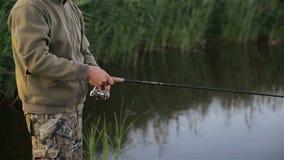钓鱼在湖的鱼人在春天 停留孤零零的钓鱼者天生单独围拢 他有休息 股票录像