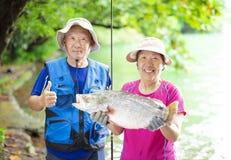 钓鱼在湖边的愉快的资深夫妇 免版税库存照片