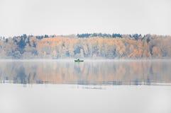 钓鱼在湖Senezh在秋天的Solnechnogorsk 雾,风,一位渔夫的剪影小船的 免版税库存照片