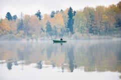 钓鱼在湖Senezh在秋天的Solnechnogorsk 雾,风,一位渔夫的剪影小船的 免版税图库摄影