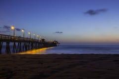 钓鱼在码头的人们在日落以后。 免版税库存照片
