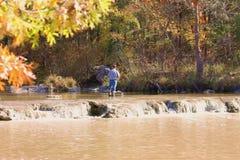 钓鱼在秋天的蓝色河 免版税库存照片