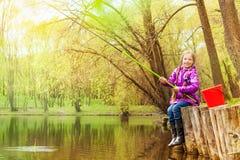 钓鱼在美丽的池塘附近的微笑的小女孩 免版税图库摄影