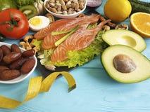 钓鱼在蓝色木背景健康食物的三文鱼日期沙拉健康柠檬养料厘米Ω 3鲕梨 免版税库存照片