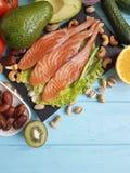 钓鱼在蓝色木背景健康食物的三文鱼沙拉Ω 3鲕梨 库存图片