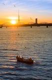 钓鱼在道加瓦河河的小船渔夫 库存照片