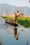 钓鱼在他的小船的渔夫在湖Inle,缅甸 库存照片