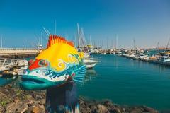 钓鱼在Corralejo口岸,其中一个的雕塑费埃特文图拉岛的标志 免版税库存图片