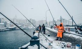 钓鱼在galata桥梁的人们在一多雪的天在冬天 免版税库存图片