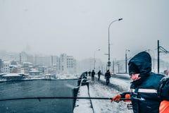 钓鱼在galata桥梁的人们在一多雪的天在冬天 库存图片