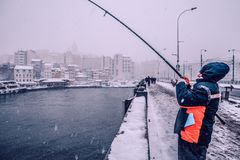 钓鱼在galata桥梁的人们在一多雪的天在冬天 库存照片