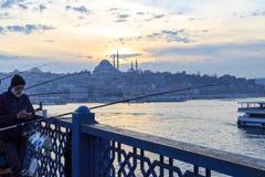 钓鱼在galata桥梁的人们有suleymaniye清真寺背景在日落期间,伊斯坦布尔 免版税库存照片