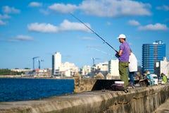 钓鱼在Malecon防波堤的人们在哈瓦那 免版税库存图片