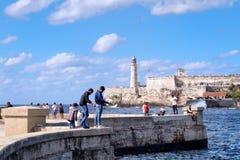 钓鱼在malecon防波堤的人们在有El Morro堡垒的哈瓦那背景的 免版税库存图片