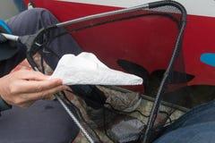 钓鱼塑料污染和垃圾的志愿者在从小船的运河外面 库存图片