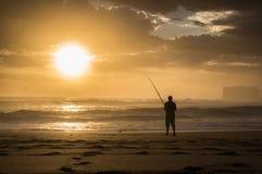钓鱼太阳的人 免版税库存照片