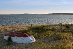 钓鱼小的日落的被放弃的海滩小船 免版税库存照片