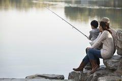 钓鱼岩石的家庭在湖 免版税库存照片
