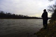 钓鱼快速流动的河河岸的早期的春天渔夫在 免版税库存图片